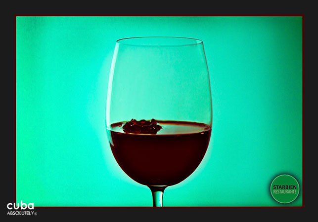 Glass of wine in  front of a green wall© Cuba Absolutely, 2014