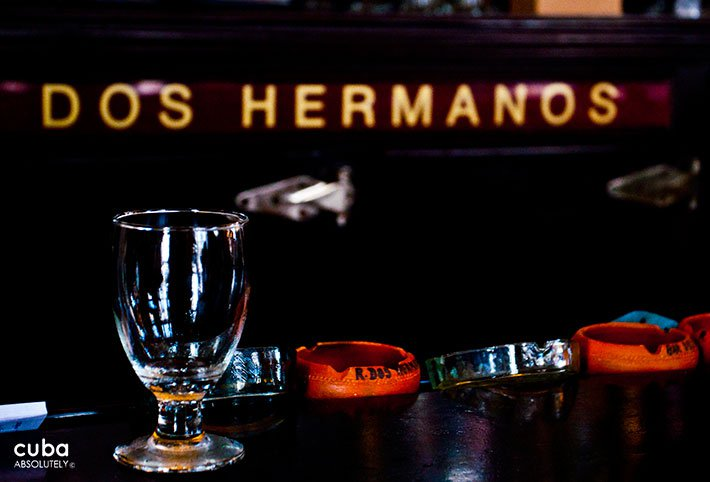 glass with the sign of Dos Hermanos restaurant behind© Cuba Absolutely, 2014