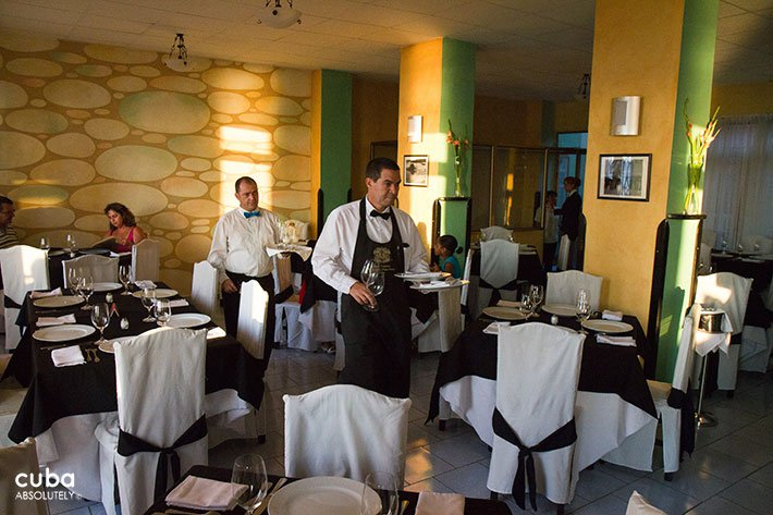waiter serving a table at restaurant with yellow walls © Cuba Absolutely, 2014