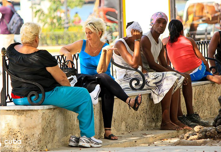 people sitting on a bank at Arms square in old havana© Cuba Absolutely, 2014