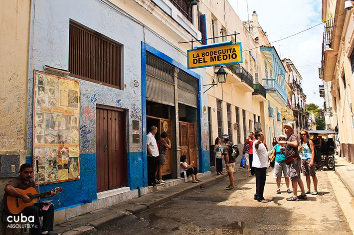 man with aguitar on the left and people standing in front La Bodeguita del Medio bar- restaurant in Old Havana © Cuba Absolutely, 2014