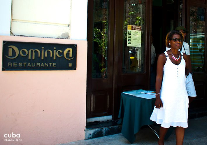 Dominica restaurant in Old Havana, woman with a white dress getting out for the front door © Cuba Absolutely, 2014