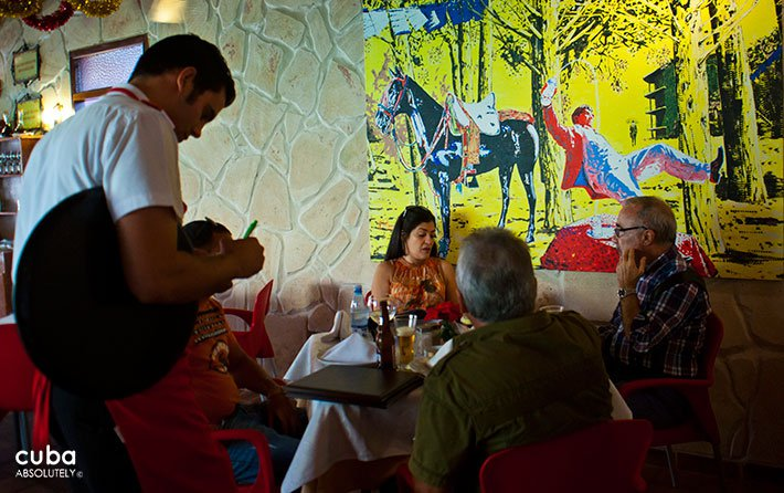 Sancho Panza restaurant in Vedado, people eating and a waiter taking the order © Cuba Absolutely, 2014