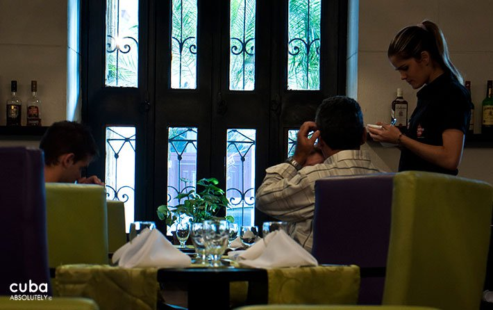 Waiter taking the order to a table at Xana restaurant in Old Havana witn green furnitures © Cuba Absolutely, 2014