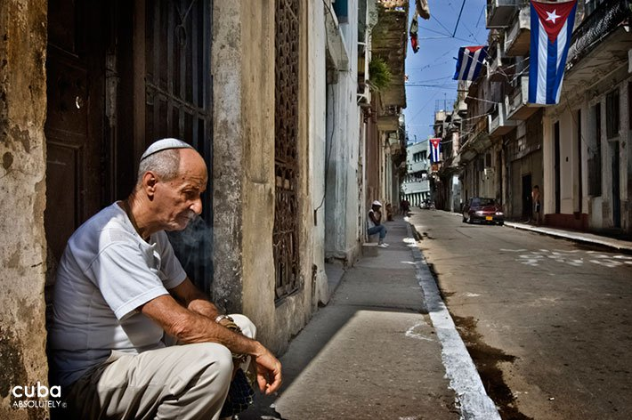Old jewish man sitting on the street in the left and a cuban flag in the back on the right © Cuba Absolutely, 2014