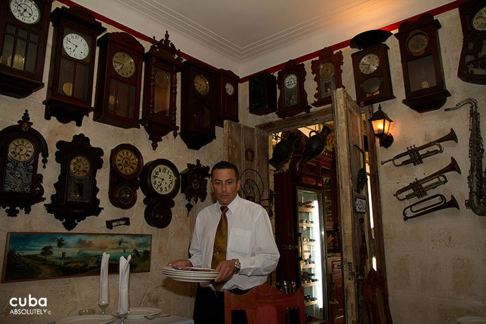 Waiter carrying dishes ina restaurant with a wall full of differents clocks © Cuba Absolutely, 2014