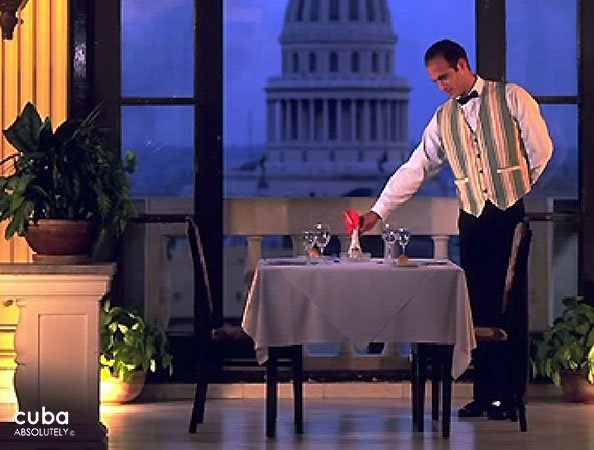 Waiter putting a red flower on a table © Cuba Absolutely, 2014