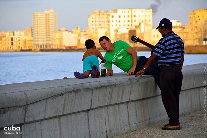 2 men and a kid sitting on the seawall © Cuba Absolutely, 2014