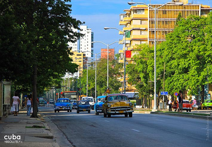Linea street in Vedado, people walking in th sidewalk, cars in the cars in the street, different buildings to both sides© Cuba Absolutely, 2014