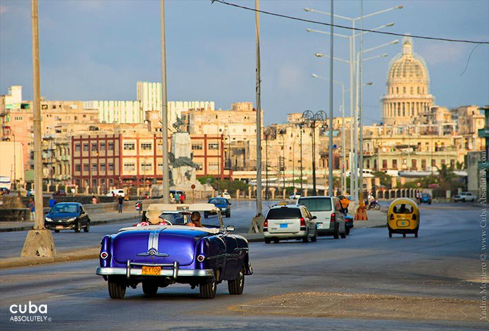 old blue car passing by the seawall © Cuba Absolutely, 2014