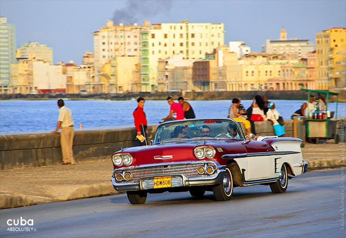 old car passing by the seawall at sunset © Cuba Absolutely, 2014
