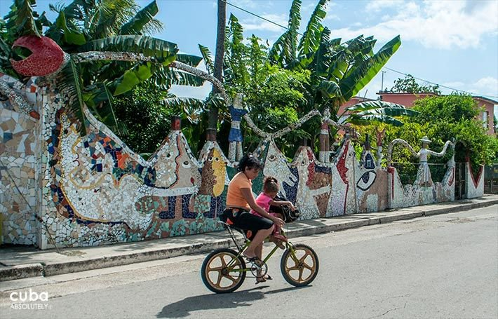 Woman with her daughter on a bicycle at Jaimanitas town, work of plastic artist Fuster © Cuba Absolutely, 2014 - 2020