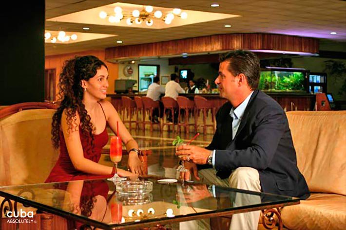 Palco hotel in Siboney, woman in red dress and man in black suit having drinks at lobby © Cuba Absolutely, 2014 - 2020