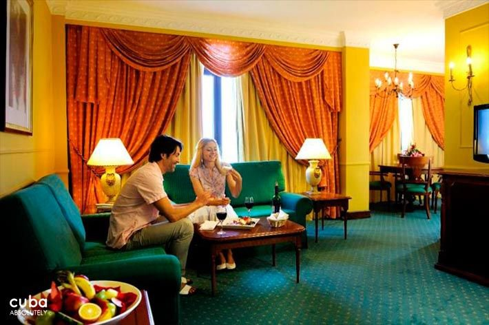 Parque Central hotel in Old Havana, couple at a yellow room with green couchs and orange curtain © Cuba Absolutely, 2014 - 2020