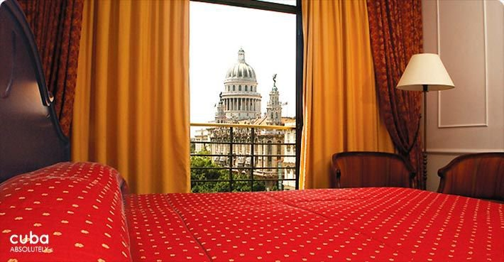 Parque Central hotel in Old Havana, view of the capitolio from a room with orange curtains and red bed © Cuba Absolutely, 2014 - 2020