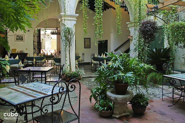 Valencia Hotel in Old Havana, iron table and chairs with color details at the interior yard © Cuba Absolutely, 2014 - 2020
