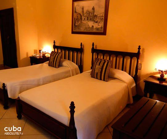 O´Farrill Palace hotel in Old Havana, room in orange with white bed  © Cuba Absolutely, 2014 - 2020