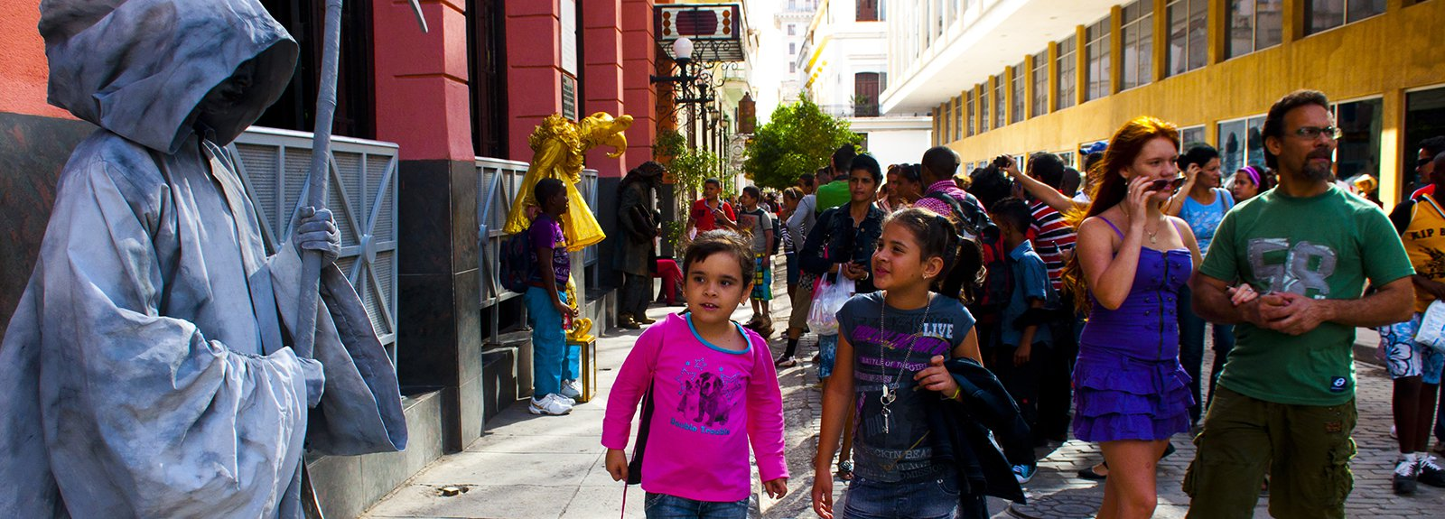 Living statue in gray on the left, child with a pink blouse on the right
