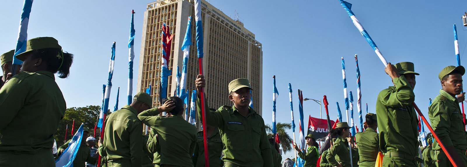 Young Military boys in green uniform carrying cuban flags