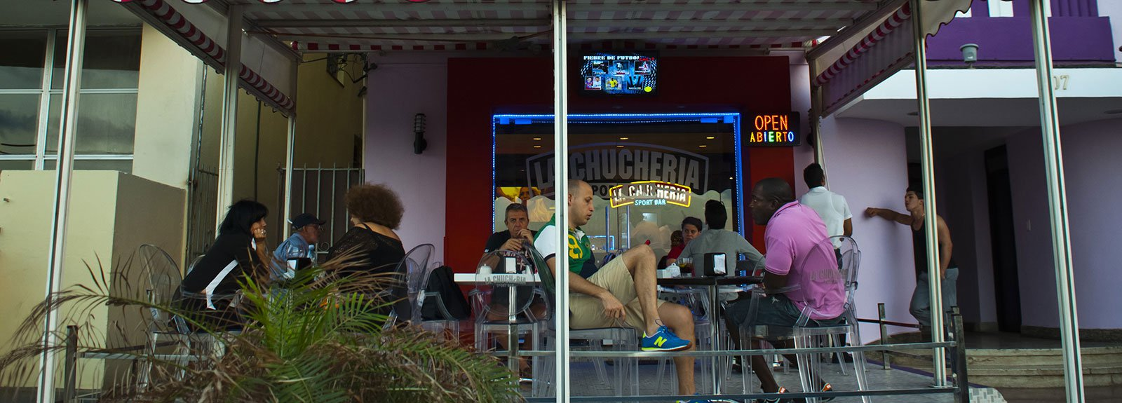 eople eating and drinking at Chucheria restaurant outdoors terrace in Vedado, transparent table and chairs