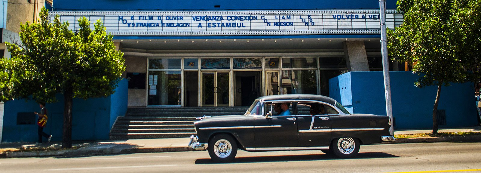 Riviera cinema, black old car passing by the street