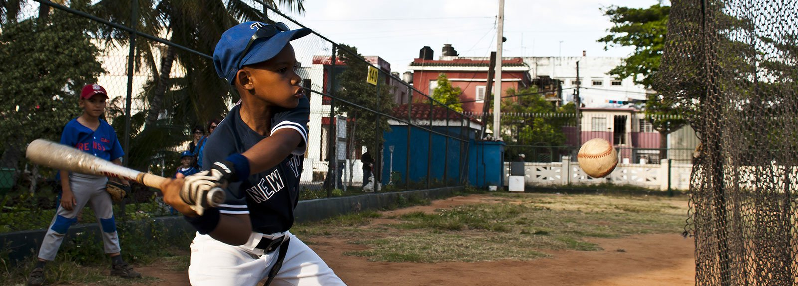 Kid playing baseball with a white and blue uniform