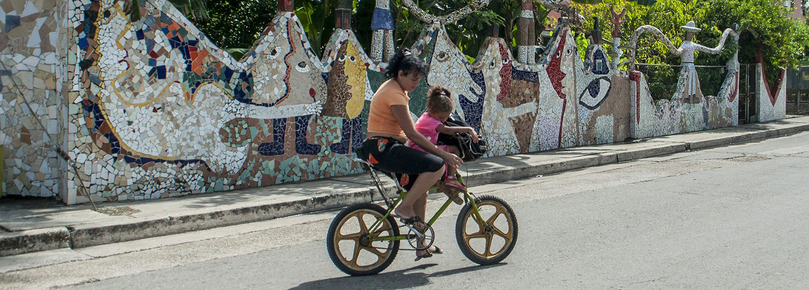Woman on a bycicle carrying a child