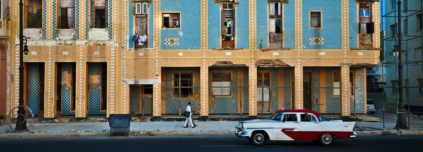 Yellow and blue building with an old car white and red park in front