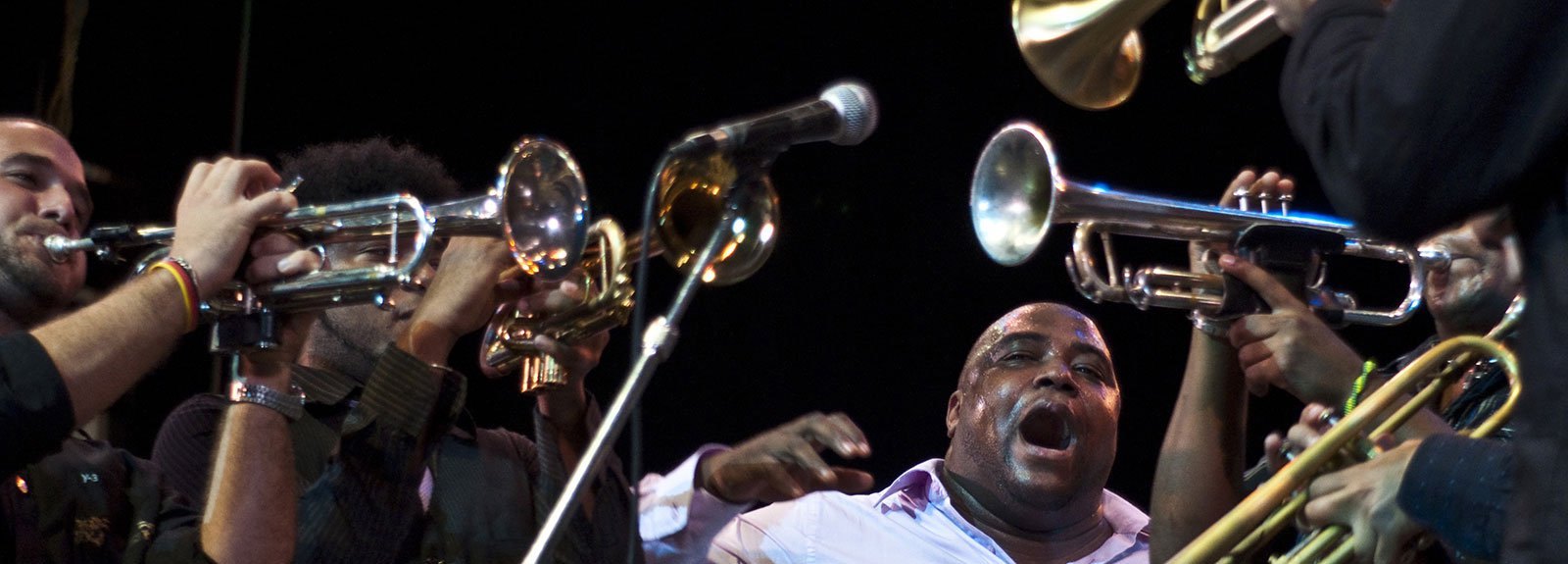 Alexander Abreu surround by trumpets on a Jazz festival