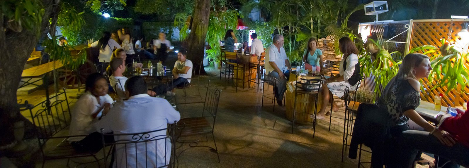 People at Espacios bar outdoor, iron and wood chairs and trees