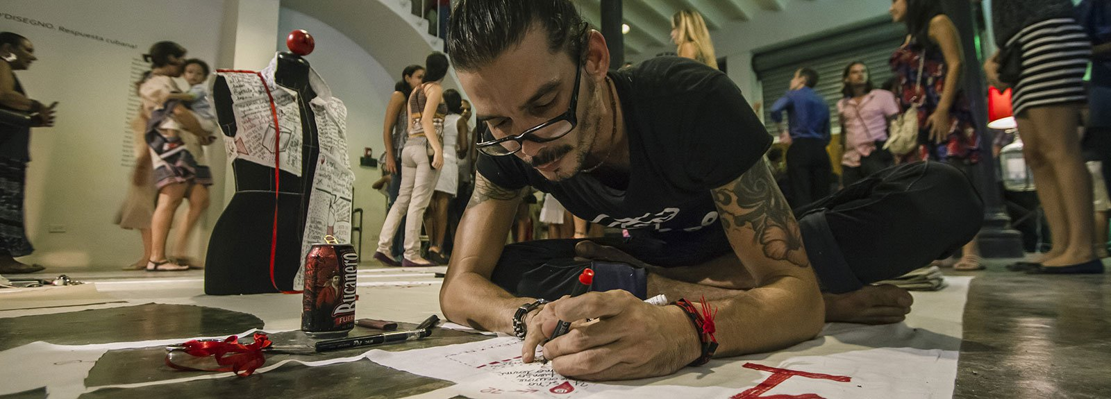 Man writing on a paper in the floor on a exhibition at factoria habana gallery