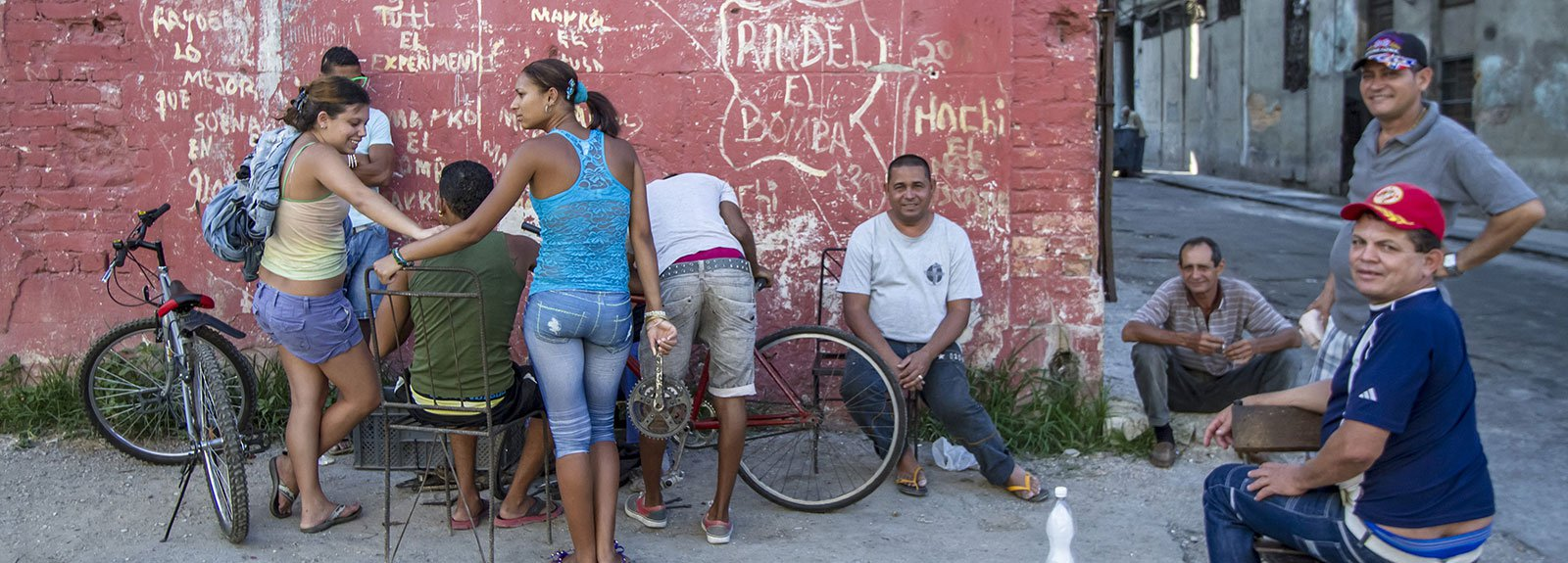 People gattered in a corner against a red wall with chairs and bicycles