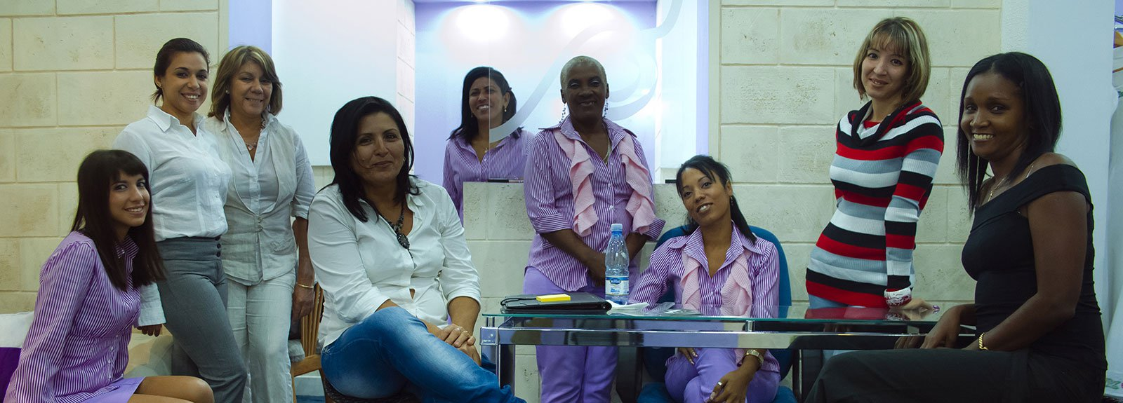 Group of woman sitting on a shop wearing violet cloth