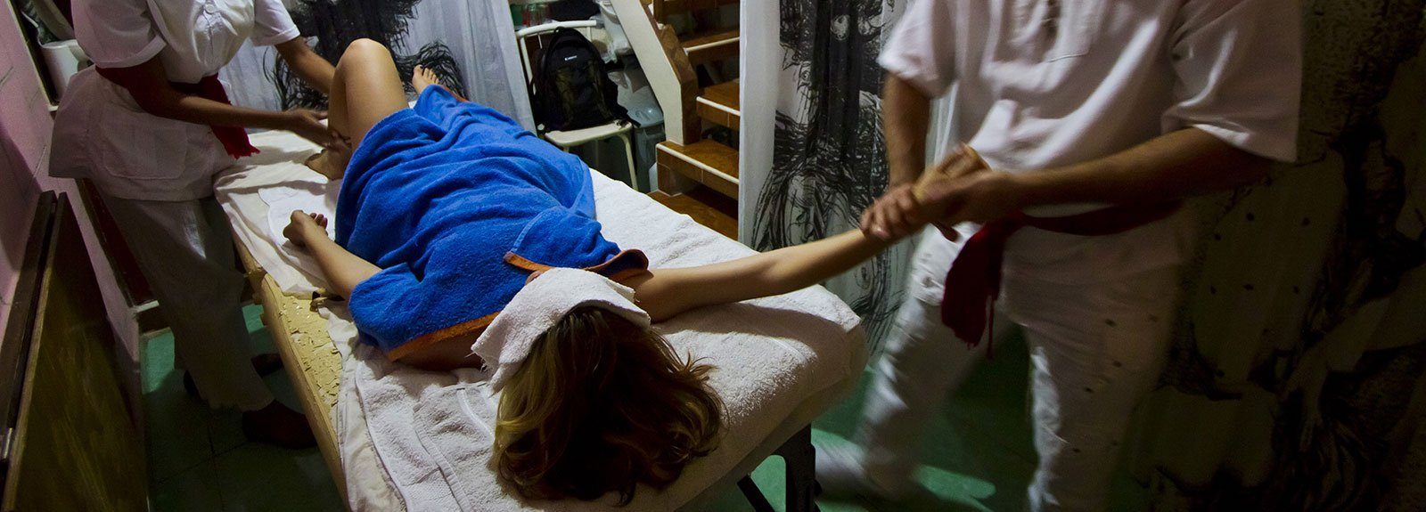 Man and woman dress in white making a massage to a girl cover with a blue towell