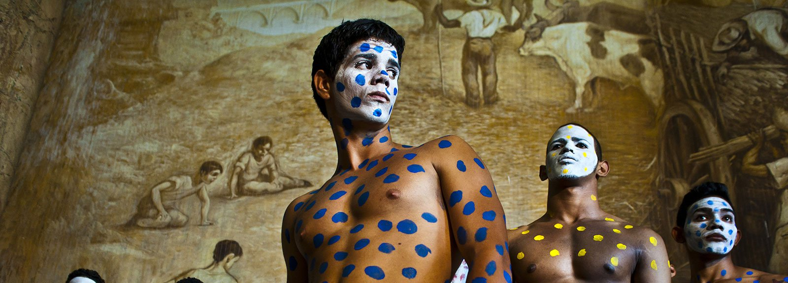 Models painted with blue and yellow spots and the face white