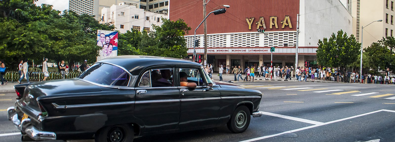 Old green car passing across Yara cinema
