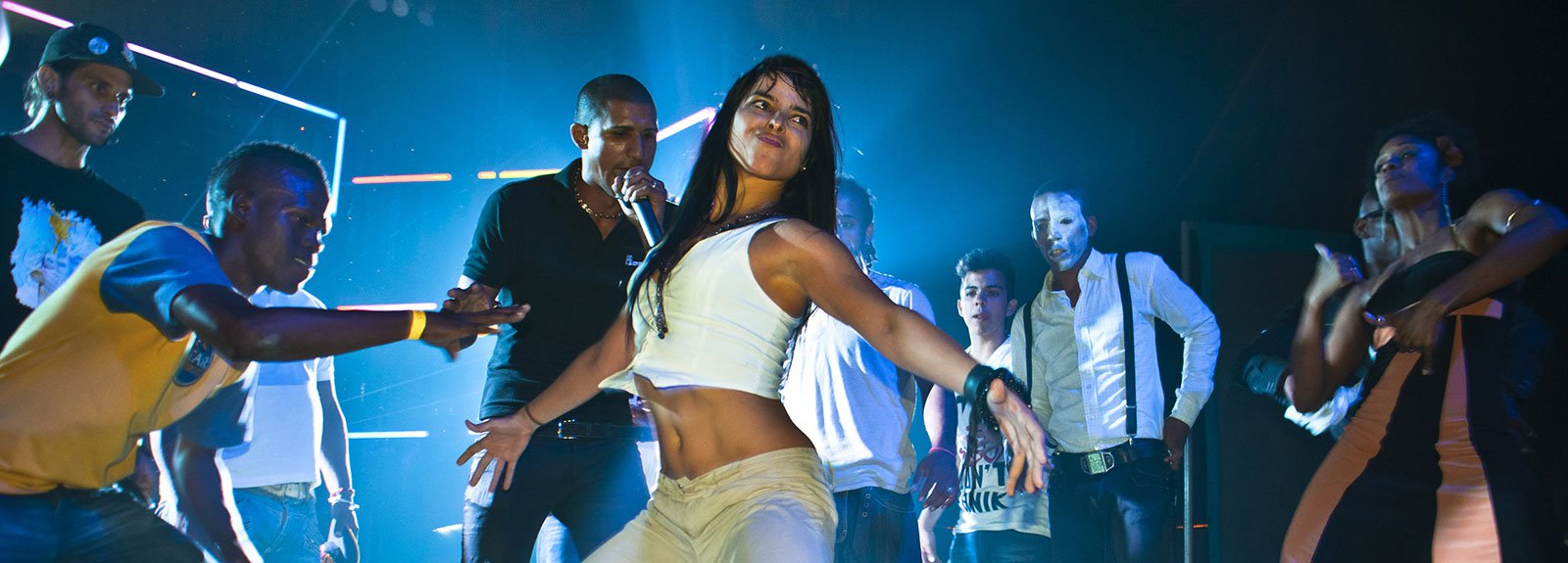 Girl in white dancing surround by people on a stage