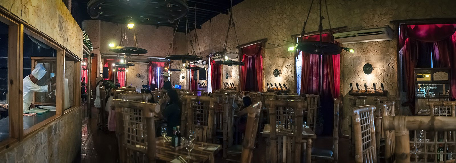 Tablao de Pancho restaurant in Old Havana, wood decoration like a rustic countryside place, band playing and people eating , waiter wearing hats