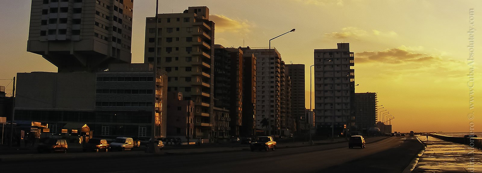 Buildings in front of seawall at sunset