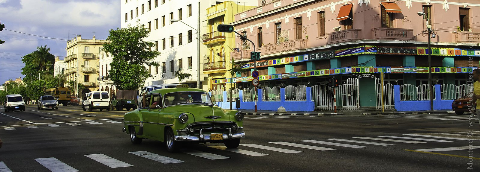 Green old car passing by the street
