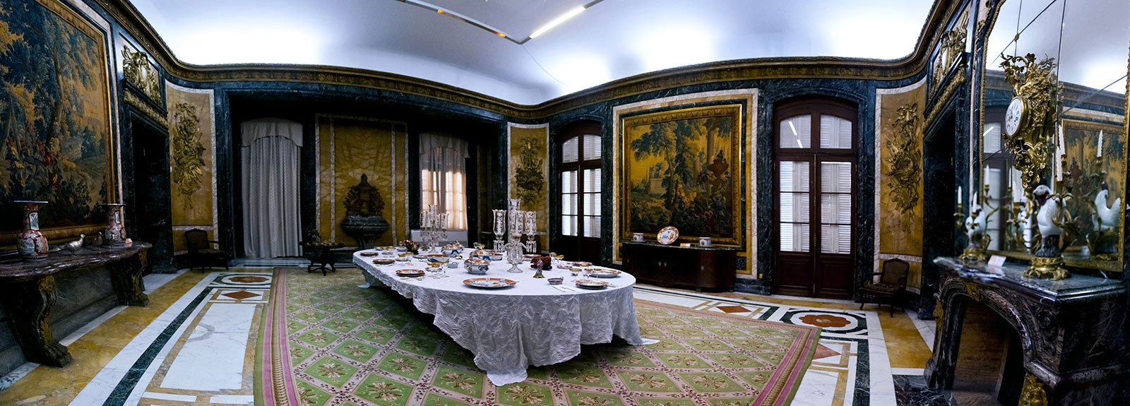 Large dinneroom with white tablecloth in the center at decorative arts museum