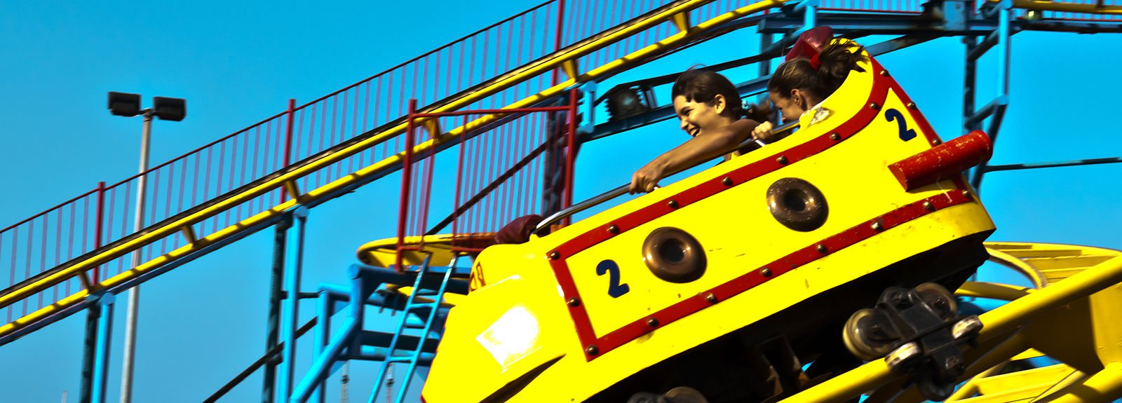 Yellow car at rollercoaster on Coney Island park