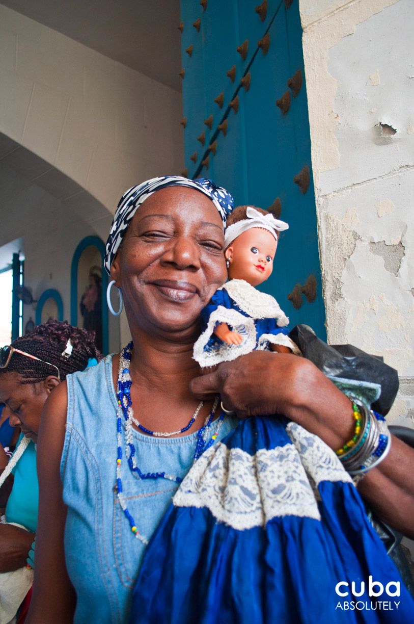Yemaya's swaying devotees mutter powerful charms and clasp their blue and white bead necklaces and amulets. Havana, Cuba