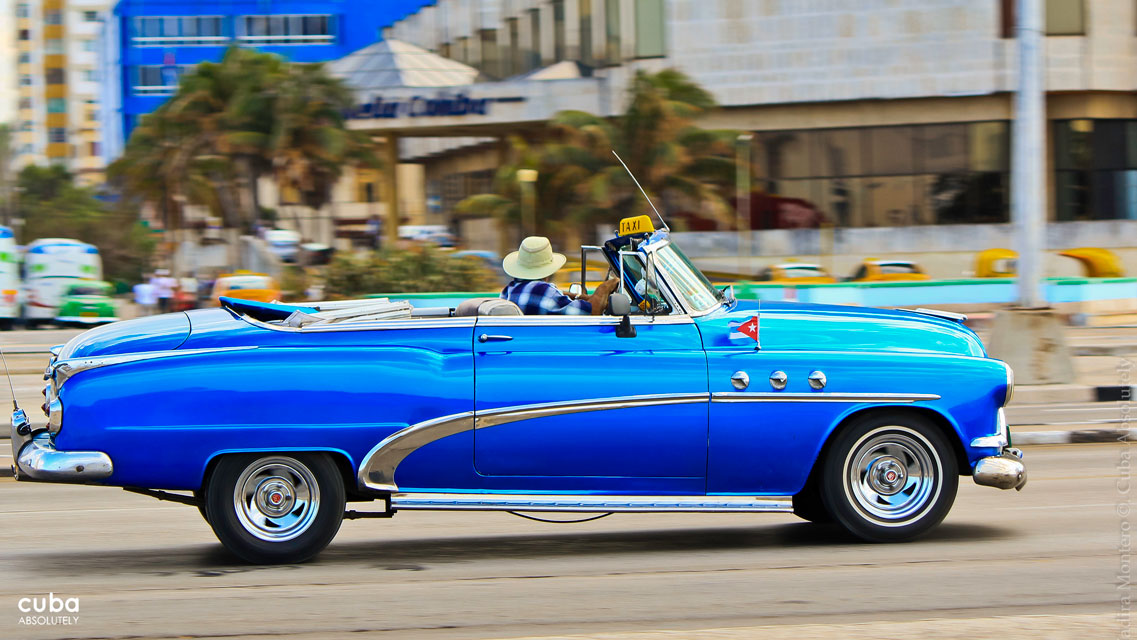 Classic American cars restored with thick coats of cerulean gloss paint growl throatily past in a cloud of blue fumes. Havana, Cuba